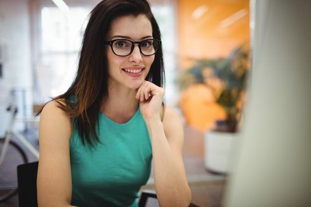 Portret pięknej kobiety wykonawczej siedzi przy biurku
