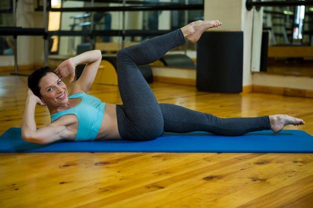 Portret pięknej kobiety wykonującej ćwiczenia rozciągające