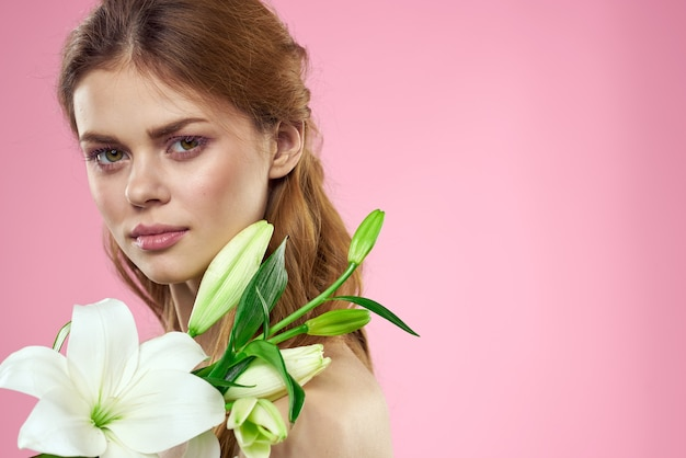 Portret pięknej kobiety z białymi kwiatami w dłoniach na różowo