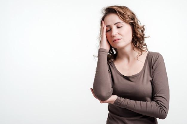 Portret pięknej kobiety, z bólem głowy lub zmartwieniem, smutny. pojedynczo na białym.