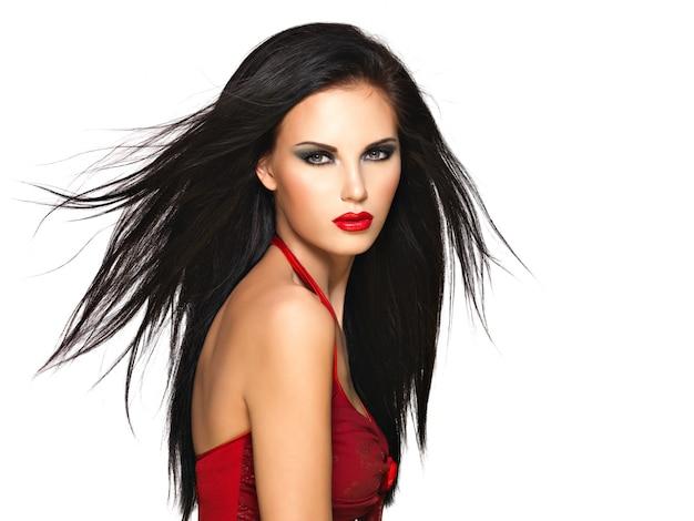 Portret pięknej kobiety z czarnymi prostymi włosami i czerwonymi ustami, makijaż wieczorowy. ładny model pozowanie w studio