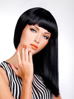 Portret pięknej kobiety z czerwonymi paznokciami i makijażem glamour i długimi czarnymi włosami
