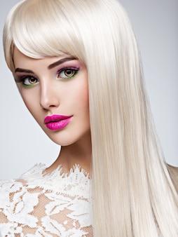 Portret pięknej kobiety z długimi białymi prostymi włosami i jasnym makijażem. twarz modelki z różową szminką. ładna dziewczyna pozuje.