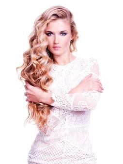 Portret pięknej kobiety z długimi blond włosami kręconymi. modelka pozowanie w białej sukni. na białym tle na białej ścianie.