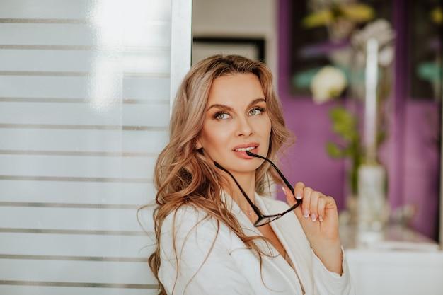 Portret pięknej kobiety z długimi kręconymi włosami w białej kurtce biurowej z okularami w gabinecie