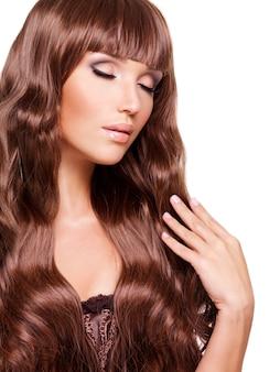 Portret pięknej kobiety z długimi rudymi włosami i zamkniętymi oczami.