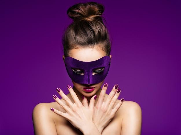 Portret pięknej kobiety z fioletowymi paznokciami i fioletową maską teatralną na twarzy.