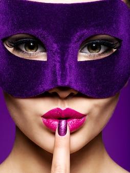 Portret pięknej kobiety z fioletowymi paznokciami i maską teatralną na twarzy.