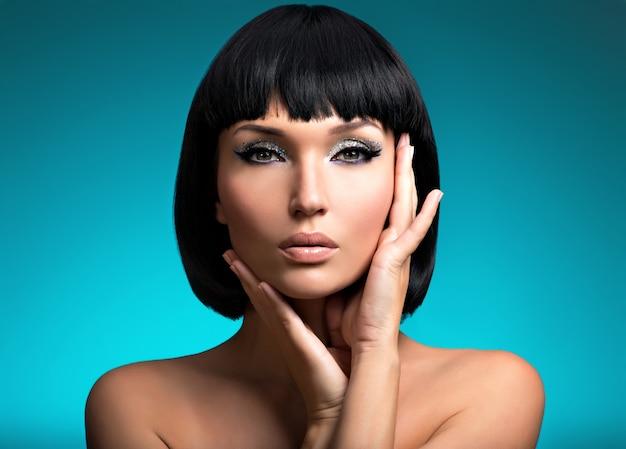 Portret pięknej kobiety z fryzurą bob. twarz modelki z kreatywnym makijażem