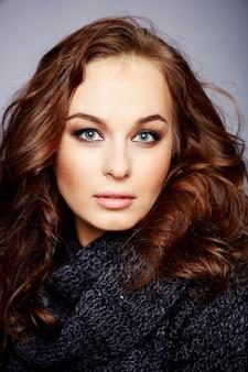 Portret pięknej kobiety z fryzurą długie sprężyste curles i profesjonalny makijaż.