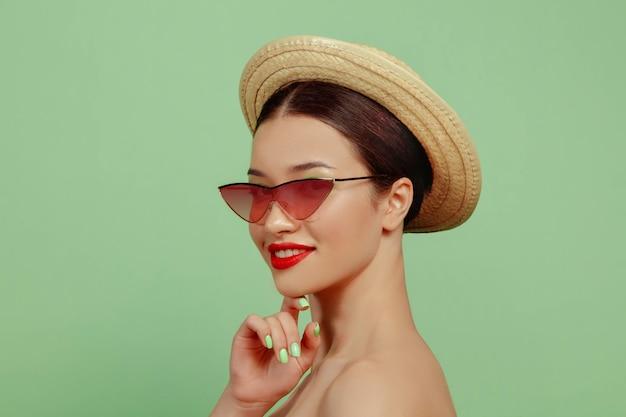 Portret pięknej kobiety z jasny makijaż, czerwone okulary i kapelusz na zielonej przestrzeni. stylowa i modna marka i fryzura. kolory lata
