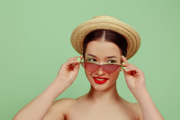 Portret pięknej kobiety z jasny makijaż, czerwone okulary i kapelusz na zielonym studio