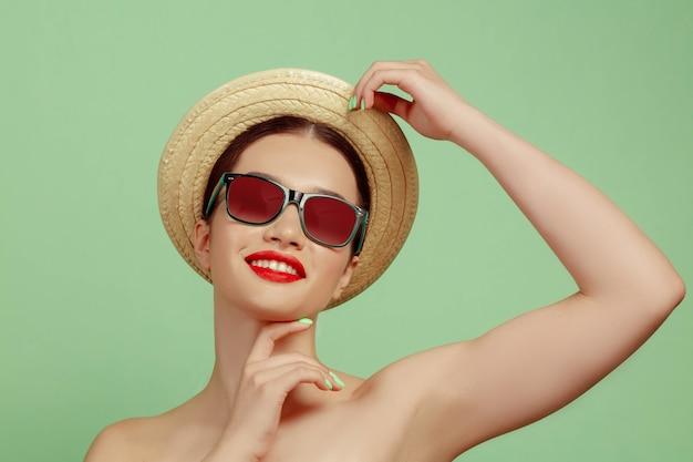 Portret pięknej kobiety z jasny makijaż, kapelusz i okulary przeciwsłoneczne na zielonej przestrzeni. stylowa i modna marka i fryzura. kolory lata