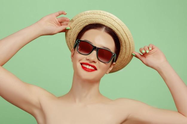 Portret pięknej kobiety z jasny makijaż, kapelusz i okulary przeciwsłoneczne na zielonym studio