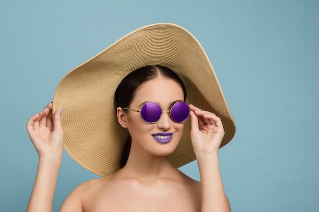 Portret pięknej kobiety z jasny makijaż, kapelusz i okulary przeciwsłoneczne. stylowa i modna marka i fryzura.