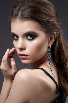 Portret pięknej kobiety z kolczykami i czarną sukienką