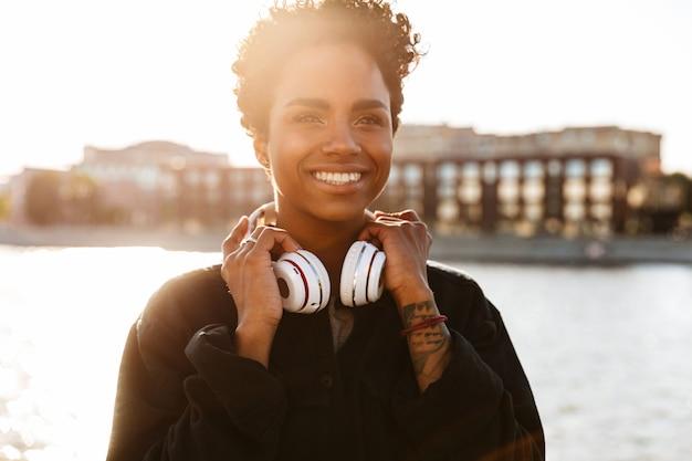 Portret pięknej kobiety z kręconą fryzurą afro trzymającą słuchawki podczas spaceru wzdłuż brzegu rzeki