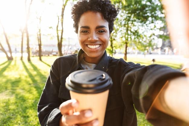 Portret pięknej kobiety z kręconymi włosami uśmiecha się i trzyma plastikową filiżankę kawy podczas spaceru po parku miejskim