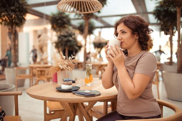 Portret pięknej kobiety z kubkiem kawy w dłoniach w kawiarni miejskiej