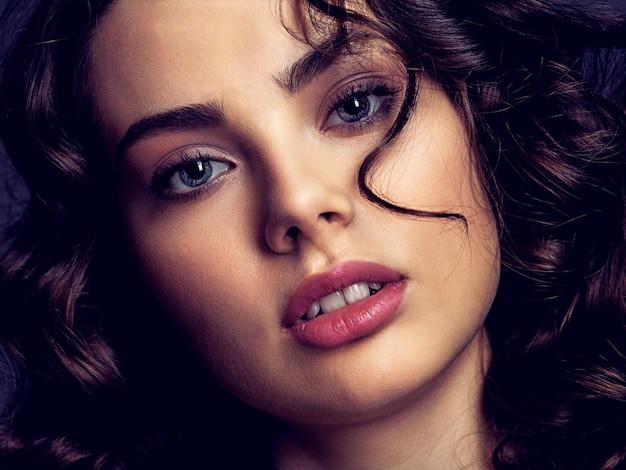 Portret pięknej kobiety z makijażem smoky eye. seksowna i wspaniała brunetka kobieta z kręconymi włosami. portret atrakcyjne kobiety pozowanie. modelka