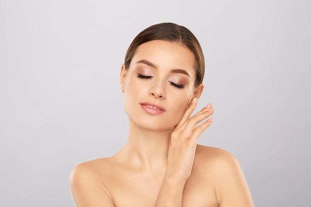 Portret pięknej kobiety z naturalnym uzupełnić dotykając jej twarzy.