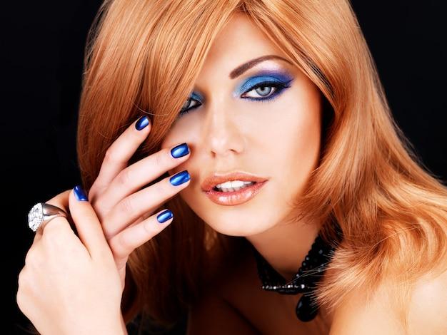 Portret pięknej kobiety z niebieskimi paznokciami, niebieskim makijażem i długimi rudymi włosami na czarnej ścianie