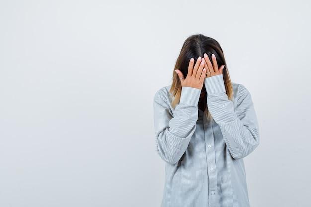 Portret pięknej kobiety z rękami na głowie pochylił się w koszuli i wygląda na przygnębiony widok z przodu