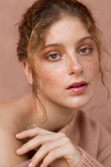Portret pięknej kobiety z różowym swetrem i nagim ramieniem