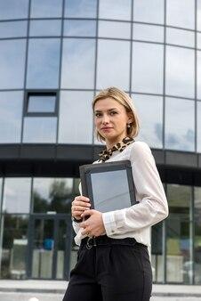 Portret pięknej kobiety z tabletem na zewnątrz, w pobliżu dużego centrum biurowego