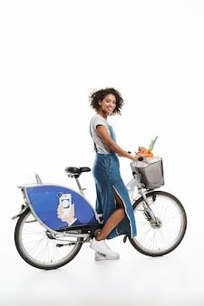 Portret pięknej kobiety z torbą na zakupy uśmiecha się podczas jazdy na rowerze na białym tle nad białą ścianą