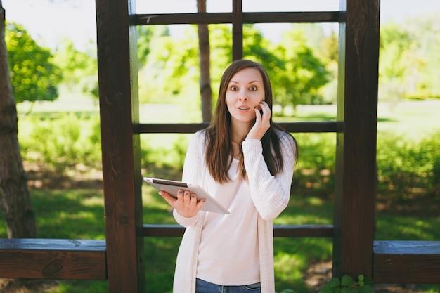 Portret pięknej kobiety z uroczym uśmiechem na sobie lekkie ubranie. ładna dziewczyna trzyma komputer typu tablet pc, czytanie wiadomości w parku miejskim na ulicy na zewnątrz na wiosnę natura. koncepcja stylu życia.