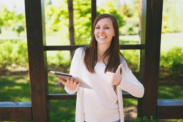 Portret pięknej kobiety z uroczym uśmiechem w ubranie pokazujące aprobaty. dziewczyna trzyma komputer typu tablet pc, czytanie wiadomości w parku miejskim na ulicy na zewnątrz na wiosnę natura. koncepcja stylu życia.