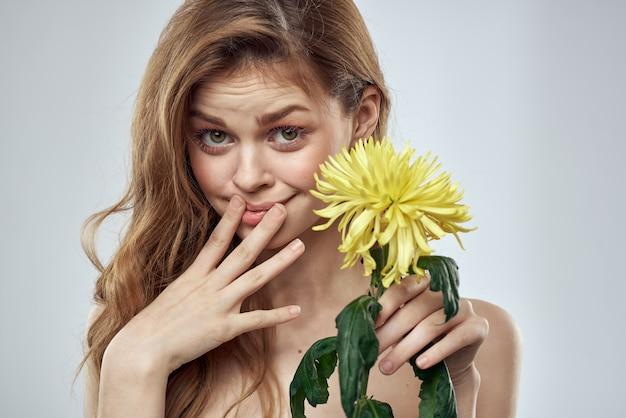 Portret pięknej kobiety z żółtym kwiatem na lekkim uroczym uśmiechu modelu rude włosy