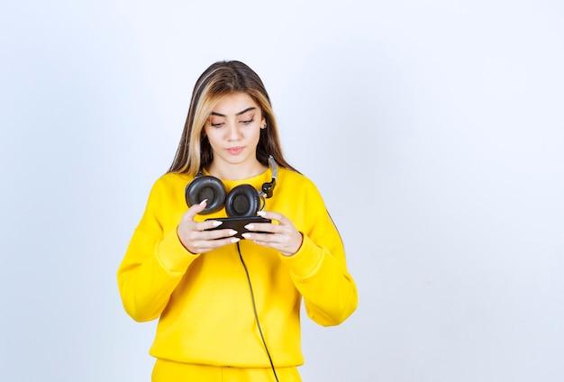 Portret pięknej kobiety ze słuchawkami przy użyciu telefonu komórkowego