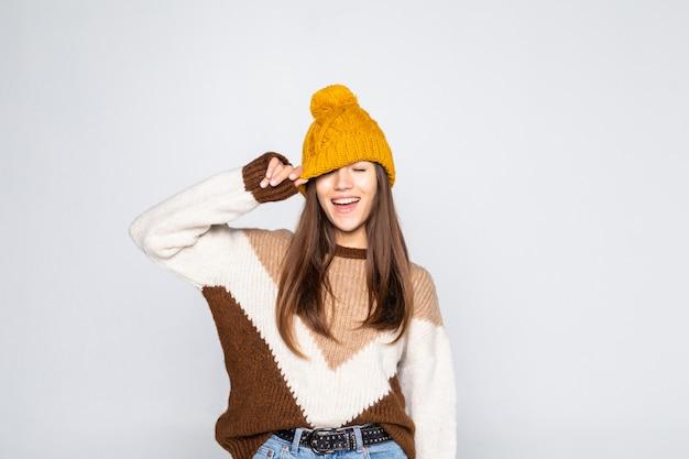 Portret pięknej kobiety zimą. uśmiechnięta dziewczyna jest ubranym ciepłych ubrania ma zabawa kapelusz i pulower odizolowywających na biel ścianie