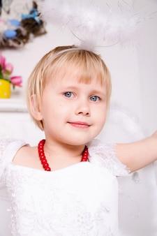 Portret pięknej księżniczki w białej sukni z białym nimbem i skrzydłami