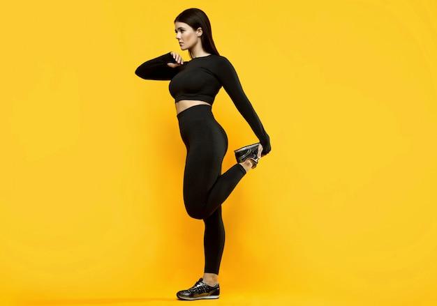 Portret pięknej latynoski pozytywne ciało kobiety w czarnym kombinezonie sportowym, ćwiczenia na żółto