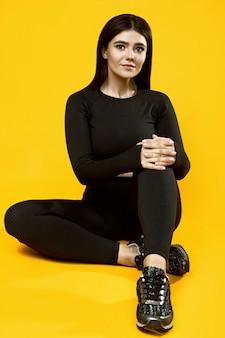 Portret pięknej latynoski z pozytywnym ciałem w czarnym kombinezonie sportowym, pozowanie na żółto