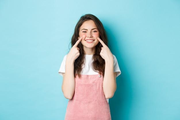 Portret pięknej letniej dziewczyny szturchającej policzki, pokazującej dołeczki i uśmiechnięte białe zęby, stojącej na niebieskim tle