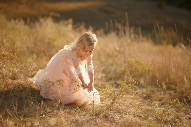 Portret pięknej małej dziewczynki księżniczki w różowej sukience.