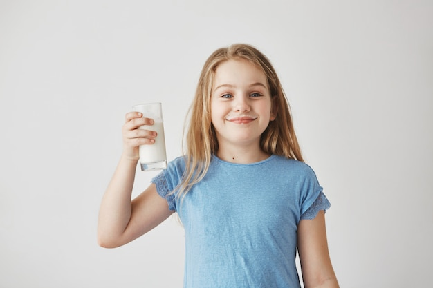 Portret pięknej małej dziewczynki o blond włosach i niebieskich oczach, uśmiechając się, trzymając w ręku szklankę mleka, będąc szczęśliwym po ulubionym drinku.