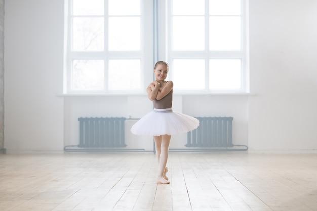 Portret pięknej małej dziewczynki w sukience tutu stojącej w pozie baletowej podczas jej treningu w szkole tańca