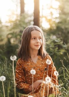 Portret pięknej małej dziewczynki wśród białych dmuchawców