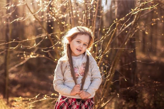 Portret pięknej małej dziewczynki z długimi włosami w lesie na przyrodę