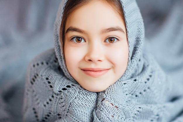 Portret pięknej małej dziewczynki z ukrytym na głowie