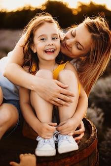 Portret pięknej matki i jej córki, podczas gdy dziewczyna patrzy na aparat, śmiejąc się, podczas gdy matka obejmuje ją od tyłu i patrzy na nią przed zachodem słońca.