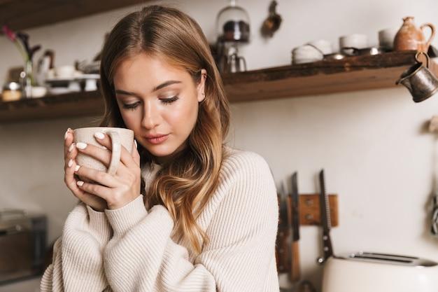 Portret pięknej, miłej kobiety noszącej zwykłe ubrania, pijącej kawę i patrzącej w dół w przytulnej kuchni