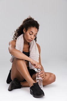 Portret pięknej młodej afrykańskiej sportsmenki odpoczynku po treningu na białym tle na szarej ścianie, woda pitna