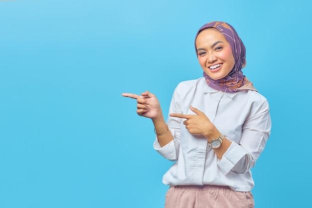Portret pięknej młodej azjatki uśmiechniętej, gestykulującej i wskazującej na pustą przestrzeń