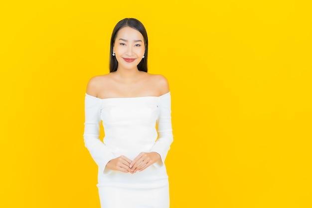 Portret pięknej młodej azjatyckiej kobiety biznesu uśmiechając się z białą sukienką na żółtej ścianie